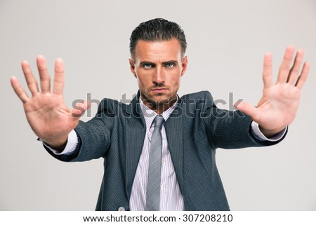 Portrait of a confident businessman showing stop gesture with palms isolated on a white background - stock photo