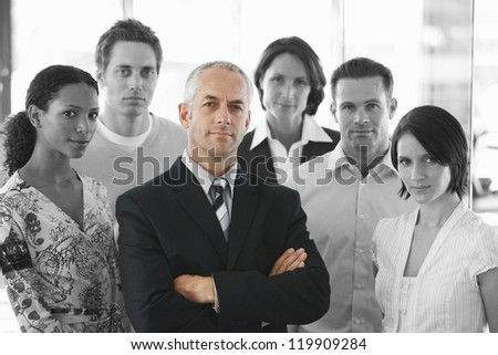 Portrait of a confident businessman standing arms crossed with office workers - stock photo