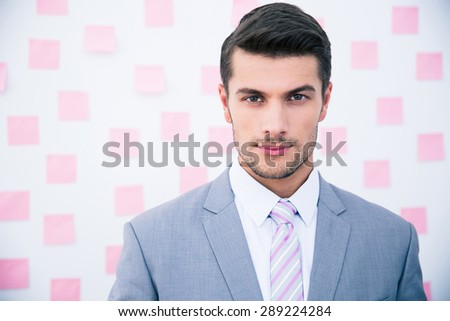 Portrait of a confident businessman standing in office and looking at camera - stock photo