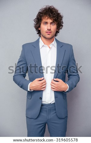 Portrait of a confident businessman standing over gray background and looking at camera - stock photo