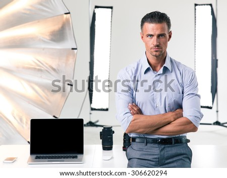 Portrait of a confident businessman standing with arms folded in studio - stock photo