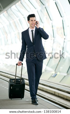 Portrait of a confident businessman talking on mobile phone at metro station - stock photo