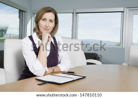 Portrait of a confident businesswoman sitting at desk - stock photo