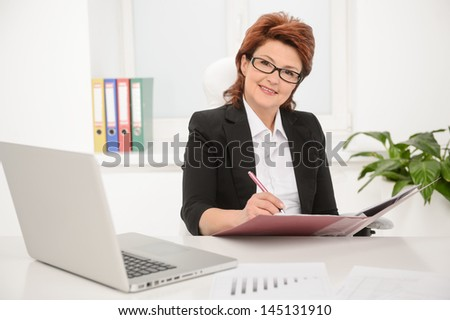 Portrait of a confident, businesswoman working on documents in office - stock photo