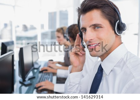 Portrait of a confident call center agent with his team working behind