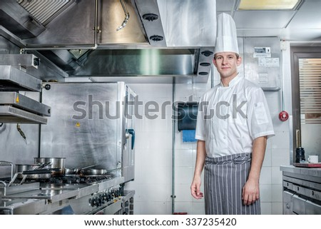 Portrait of a confident chef. Young chef preparing a delicious meal in the kitchen of the restaurant. - stock photo