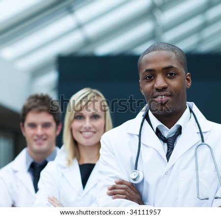 Portrait of a confident ethnic doctor leading his team - stock photo