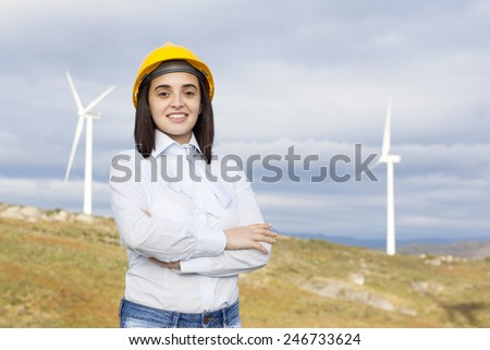 Portrait of a confident female engineer standing at wind turbine site