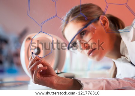 Portrait of a confident female health care professional in his working environment writing structural chemical formula on a glass board. - stock photo