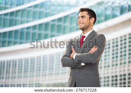 Portrait of a confident handsome young businessman with folded arms - stock photo