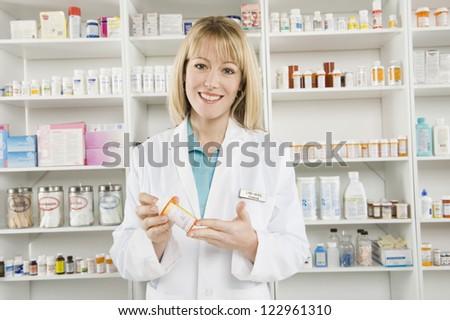 Portrait of a confident happy pharmacist prescribing medicine at workplace - stock photo