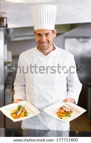 Portrait of a confident male chef with cooked food standing in the kitchen - stock photo