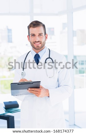 Portrait of a confident male doctor with clipboard standing in the hospital