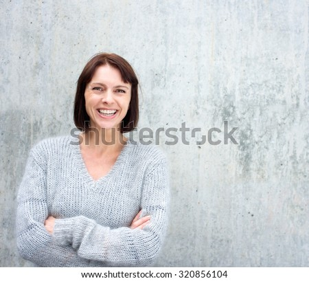Portrait of a confident older woman smiling against gray background - stock photo
