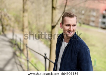 Portrait of a confident relaxed man standing on a footpath with the city behind him, a big toothy smile on a sunny day.