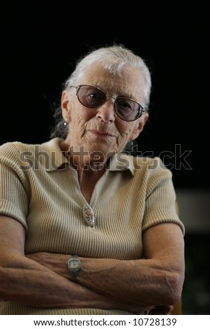 Portrait of a confident senior woman over black background - stock photo