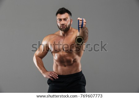 Portrait of a confident serious shirtless male bodybuilder holding gold medal isolated over gray background