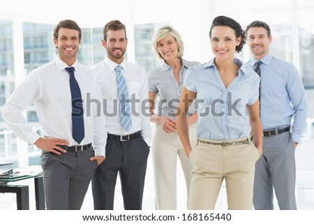 Portrait of a confident smiling business team standing in a bright office