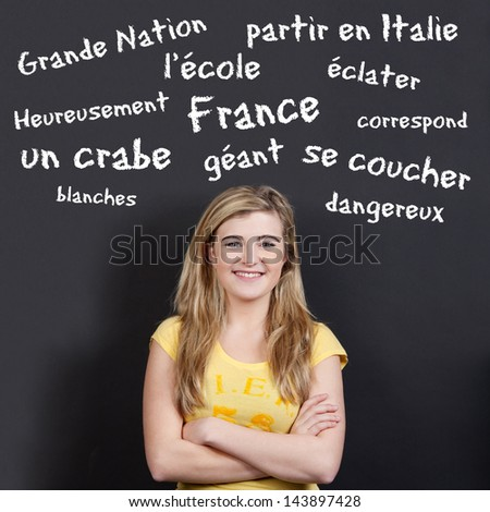 Portrait of a confident smiling teenage girl with arms crossed against French vocabulary on black background - stock photo