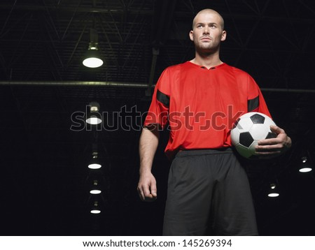 Portrait of a confident soccer player holding ball - stock photo
