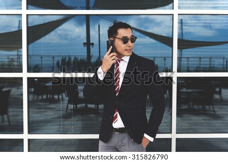 Portrait of a confident successful men entrepreneur dressed in luxury clothes having mobile phone conversation outdoors, young asian businessman talking on cellphone while standing near office window - stock photo