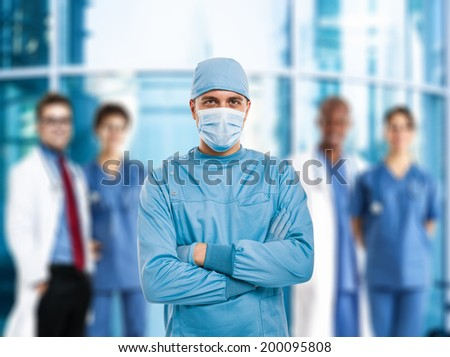 Portrait of a confident surgeon in front of a group of doctors - stock photo