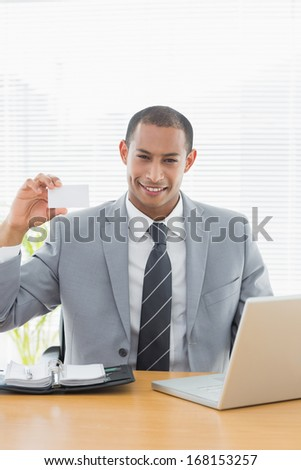 Portrait of a confident well dressed man holding business card in front of laptop at office desk