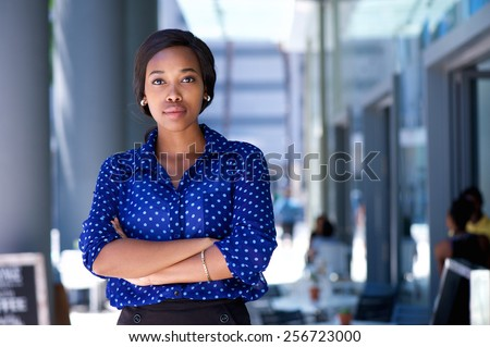 Portrait of a confident young african american woman standing in the city - stock photo