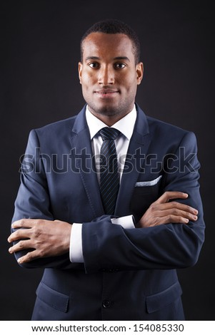 Portrait of a confident young black business man on dark background - stock photo