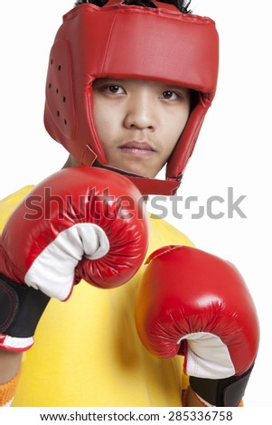 Portrait of a confident young boy wearing head protector and boxing gloves over white background
