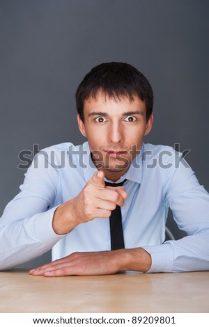 Portrait of a confident young business man in suit pointing at you while sitting at his office