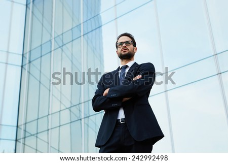 Portrait of a confident young businessman in glasses standing with crossed arms - stock photo