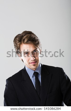 Portrait of a confident young businessman looking directly at camera - stock photo