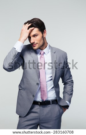 Portrait of a confident young businessman touching his hair over gray background and looking at camera - stock photo
