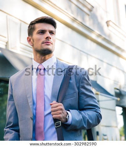 Portrait of a confident young businessman walking outdoors in town - stock photo