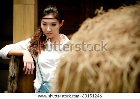 Portrait of a confident young cowgirl standing beside thatch looking for something - stock photo