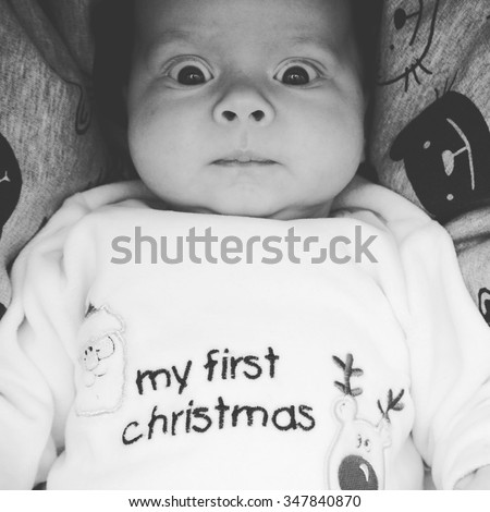 Portrait of a confused baby at his first Christmas  - stock photo