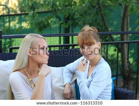 Portrait of a confused blond woman with smiling friend in street cafe - stock photo