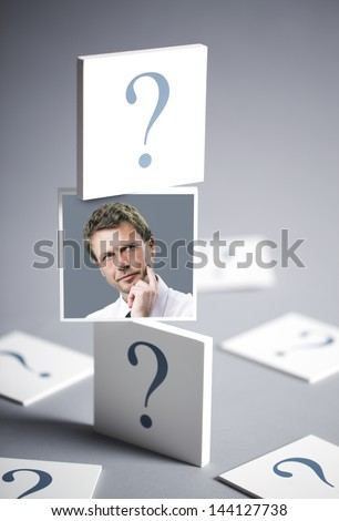 Portrait of a confused businessman surrounded by question marks - stock photo