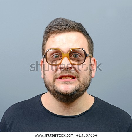Portrait of a confused chubby geek against gray background - stock photo