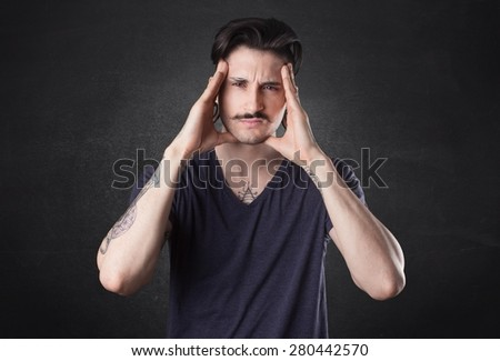 Portrait of a confused male individual with hand in hair.