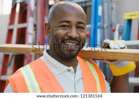 Portrait of a construction worker carrying wooden plank on shoulder with ladders in the background