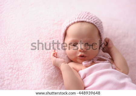 Portrait of a cooing, two week old, newborn baby girl. She is wearing a knitted bonnet and is lying on a soft, fuzzy, pink blanket. - stock photo
