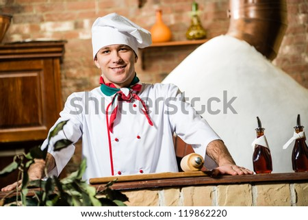 portrait of a cook, behind a stone table and looks ahead - stock photo