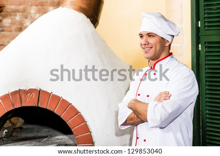 portrait of a cook in the kitchen near the wood-burning oven for pizzas, traditional cuisine - stock photo