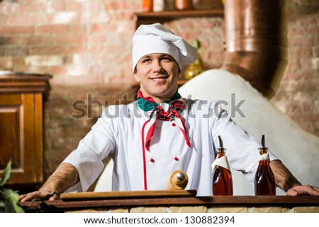 portrait of a cook, is on the traditional kitchen relies hands on the table - stock photo