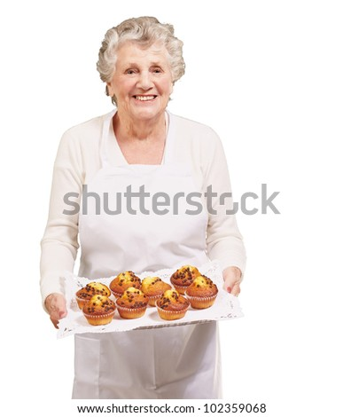 portrait of a cook senior woman holding a chocolate muffins tray over a white background - stock photo