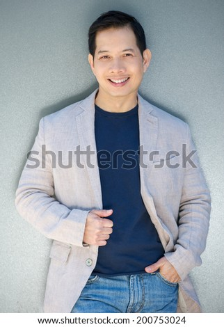 Portrait of a cool asian man posing with a smile - stock photo