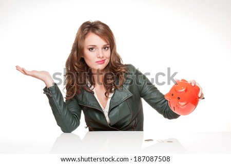 Portrait of a cool beautiful young fashionable brunette with piggy bank. - stock photo