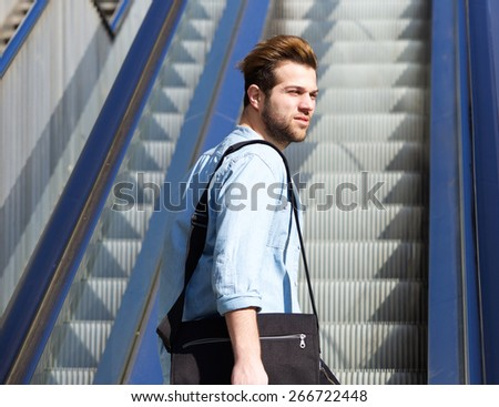 Portrait of a cool guy standing on escalator - stock photo